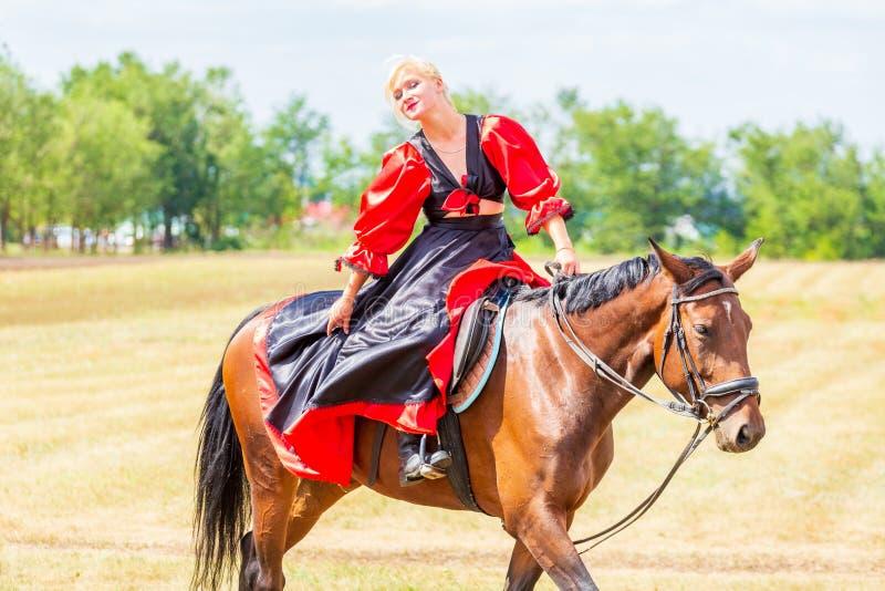Ruitersportdressuur, passage - een jong meisje in een mooie kleding zit op een paard royalty-vrije stock afbeelding