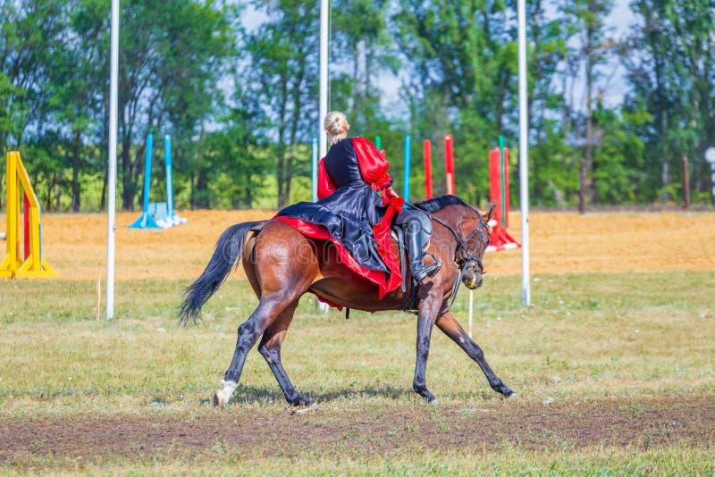 Ruitersportdressuur, passage - een jong meisje in een mooie kleding zit op een paard stock fotografie