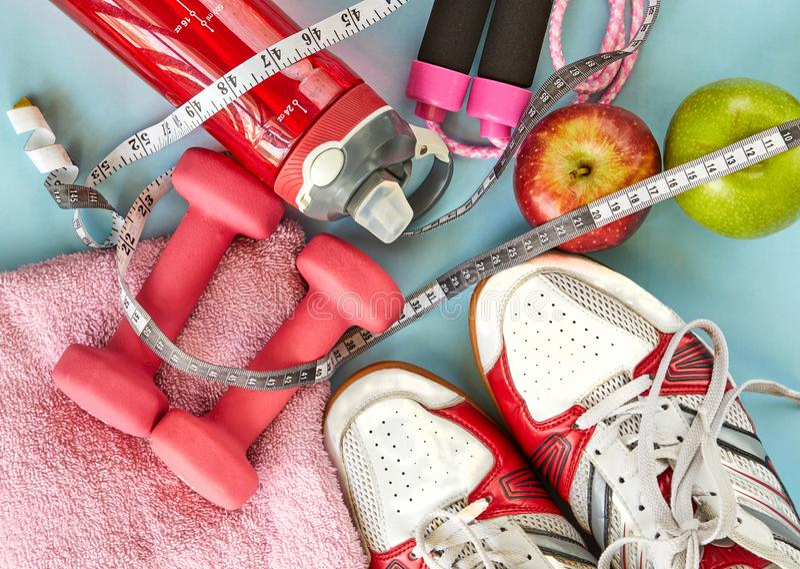 ruits, pesas de gimnasia, botella de agua, cuerda, zapatillas de deporte y metro en un fondo azul imagenes de archivo