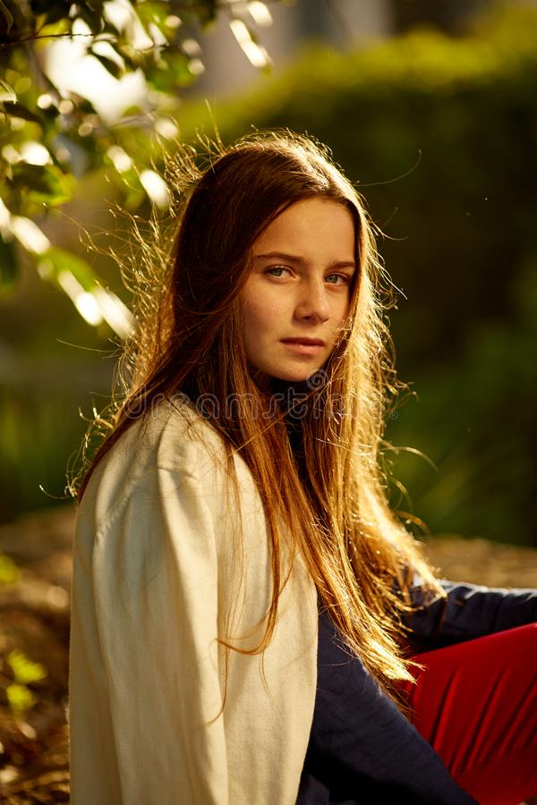Ruivo 12 anos de menina idosa que senta-se em uma rocha e em um pensamento ocupado foto de stock royalty free