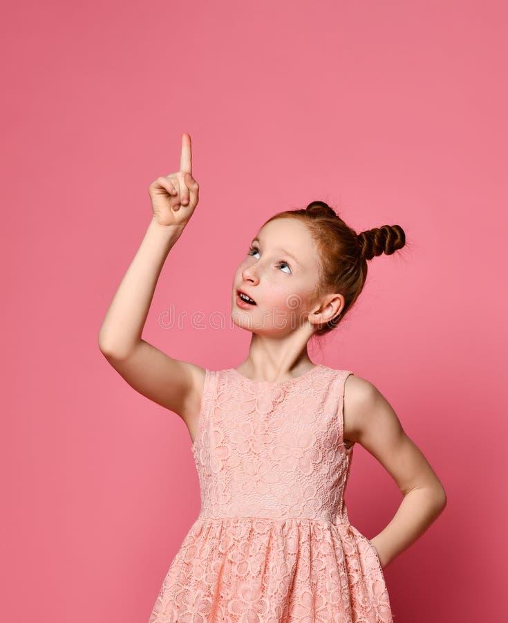 Ruivo feliz da menina no vestido cor-de-rosa que levanta com m?o no quadril ao ter uma ideia e ao olhar a c?mera imagem de stock