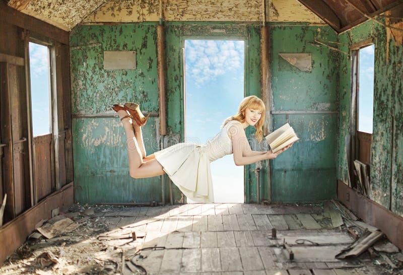 Ruivo levitando contente com o livro fotos de stock royalty free