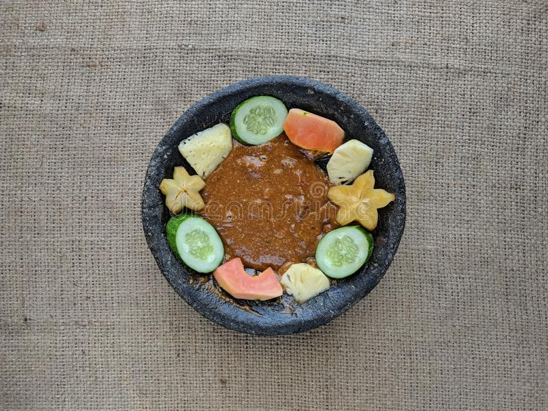 Rujak or Lotis is Indonesian tropical food, made from fresh, sliced rather large fruits, eaten with sweet chili made from java su. Gar, chili, salt. Delicious stock photo