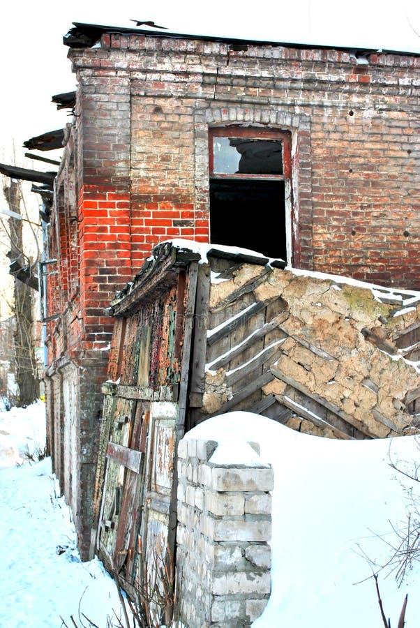 Rujnująca czerwonej cegły domu ściana z nadokienną dziurą, śnieg zakrywał ogrodzenie ścianę zdjęcie royalty free