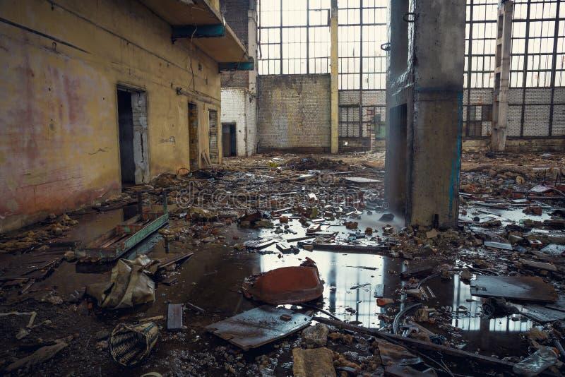 Rujnujący przemysłowy budynek z kałużami na ziemi, przerażający zaniechany magazyn zdjęcie royalty free