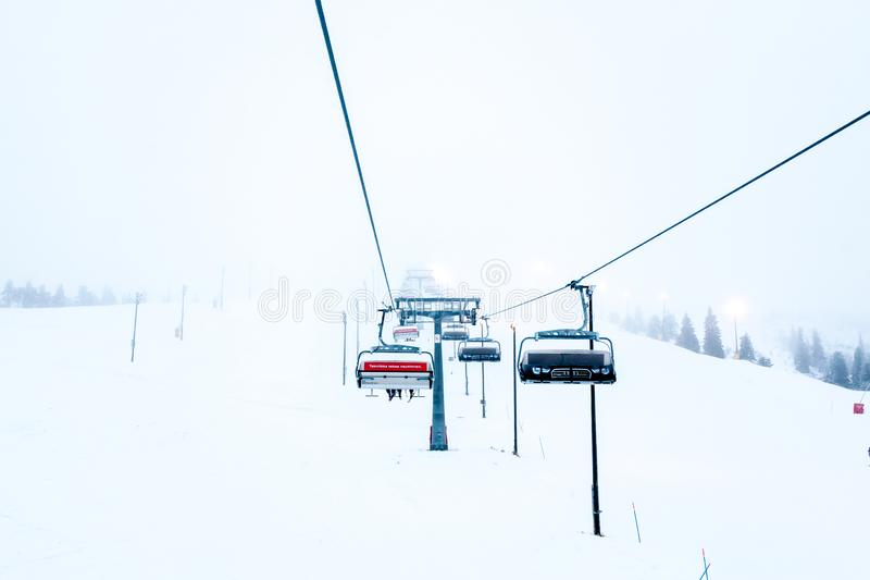 Ruka, Finnland - 24. November 2012: Skifahrer, die auf dem Stuhlskiaufzug an Ruka-Skiort an einfrierendem Tag sitzen stockbild