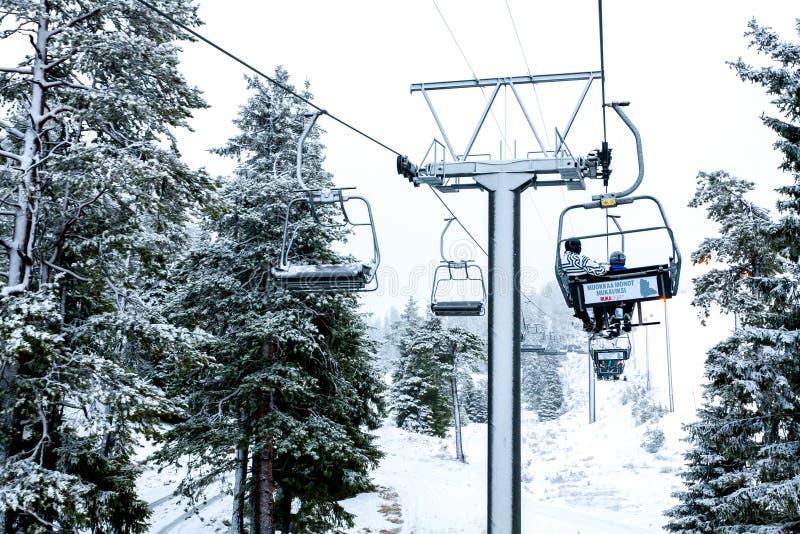Ruka, Finnland - 24. November 2012: Skifahrer sitzen auf dem Stuhlskiaufzug an Ruka-Skiort an einfrierendem Tag lizenzfreies stockbild
