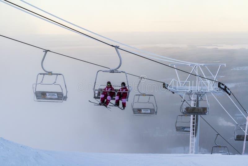 Ruka, Finnland - 27. November 2012: Skifahrer sitzen auf dem Stuhlskiaufzug an Ruka-Skiort an einfrierendem Tag stockfoto