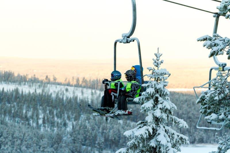 Ruka, Finnland - 27. November 2012: Skifahrer sitzen auf dem Stuhlskiaufzug an Ruka-Skiort an einfrierendem Tag lizenzfreies stockbild