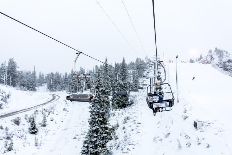 Ruka, Finnland - 24. November 2012: Skifahrer sitzen auf dem Stuhlskiaufzug an Ruka-Skiort an einfrierendem Tag lizenzfreie stockbilder