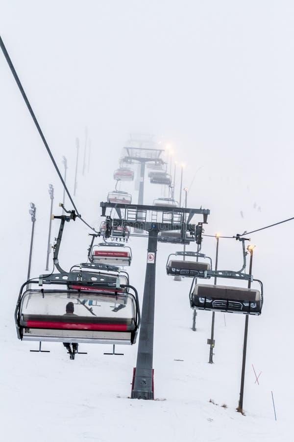 Ruka, Finnland - 24. November 2012: Skifahrer sitzen auf dem Stuhlskiaufzug an Ruka-Skiort an einfrierendem Tag lizenzfreie stockfotografie