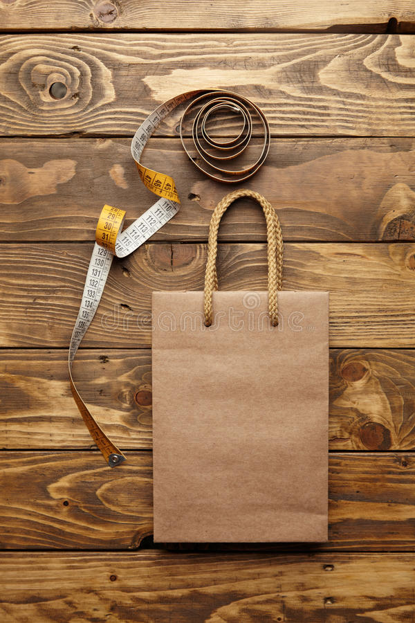 Ruler mockup set. Brown takeaway bag from thic recycled craft paper on rustic wooden table near unrolled vintage tailoring meter mockup stock images