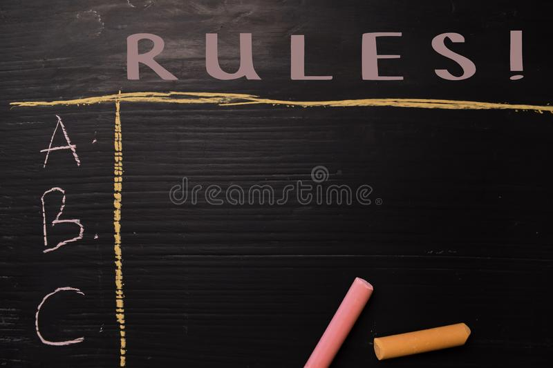 Rules! written with color chalk. Supported by an additional services. Blackboard concept royalty free stock images
