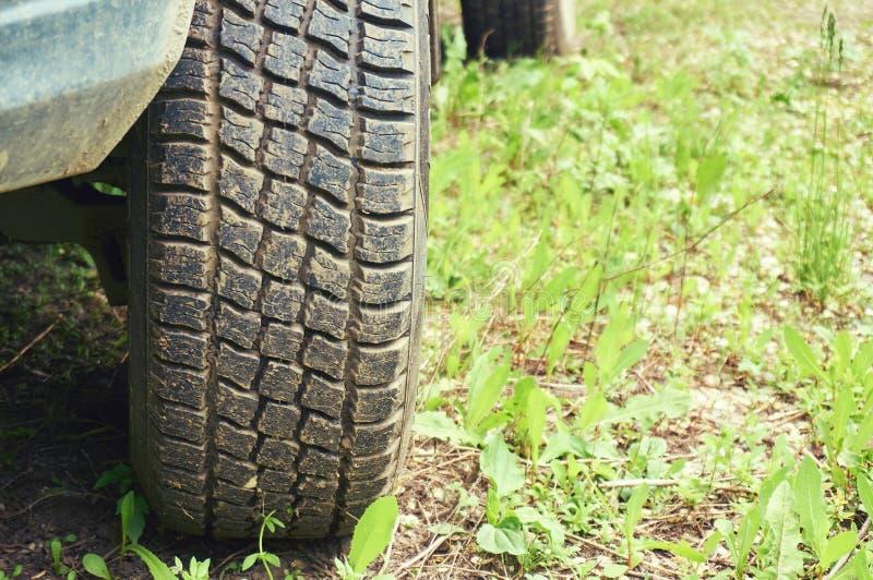 Rulla från en bilnärbild mot en bakgrund av grönt gräs abstrakt bakgrund arkivfoto