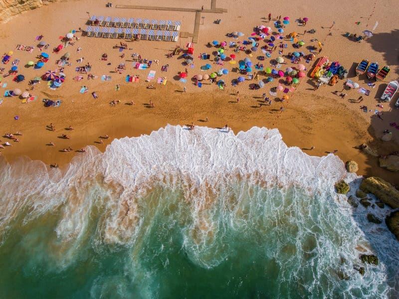 Rulla framåt vågor på stranden med turister arkivfoton