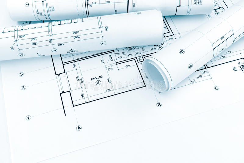 Rullande arkitektoniska plan och tekniska teckningar på husbluep royaltyfri foto