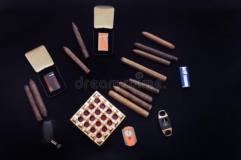 Rullande cigarrer i en grupp på svart och askamagasin med skäraren fotografering för bildbyråer