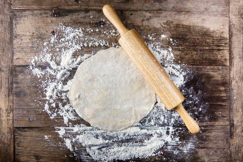 Rullande deg med kavlen på trätabellen som täckas med bakningmjöl arkivfoton