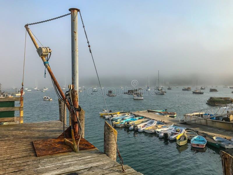 Rullande dimma över en hamn i kust- Maine royaltyfri fotografi