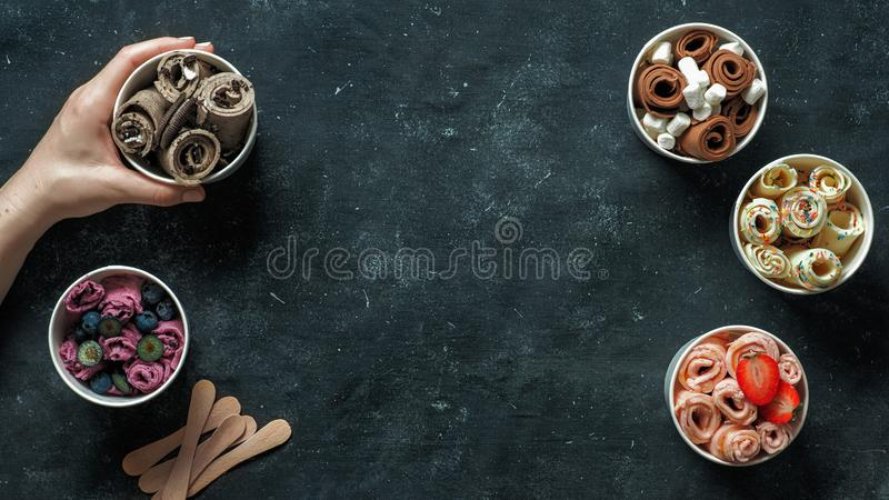 Rullande glassar i kottekoppar på mörk bakgrund arkivbilder