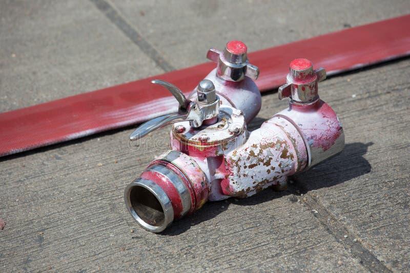 Rullande in i en slang för röd brand för rulle, brandutrustningeldsläckare r royaltyfria bilder