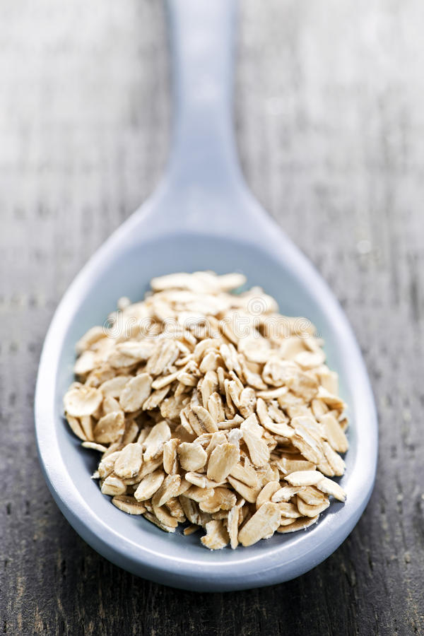 rullande oats skedar uncooked royaltyfria foton