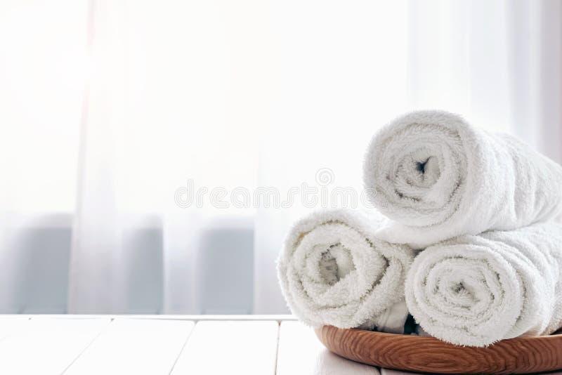 Rullande vita handdukar på trämagasinet royaltyfri foto