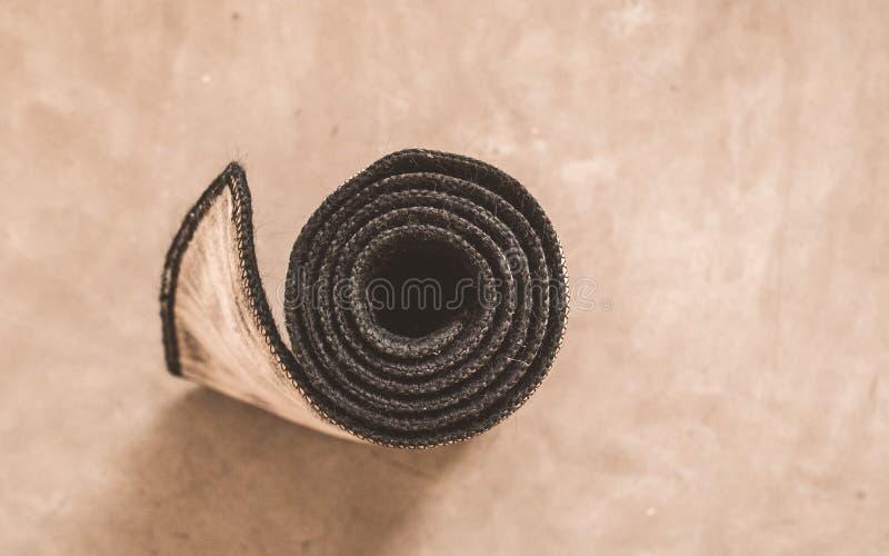 Rullande yoga som är matt efter övningen som isoleras på lantlig cementgolvbakgrund i en sportaktivitetsmitt Kondition sunt liv,  royaltyfria foton