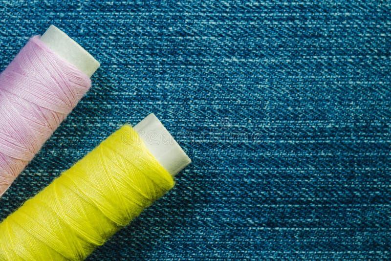 Rullar av den rosa och gula sy tråden på blå grov bomullstvill med kopieringsutrymme arkivbilder