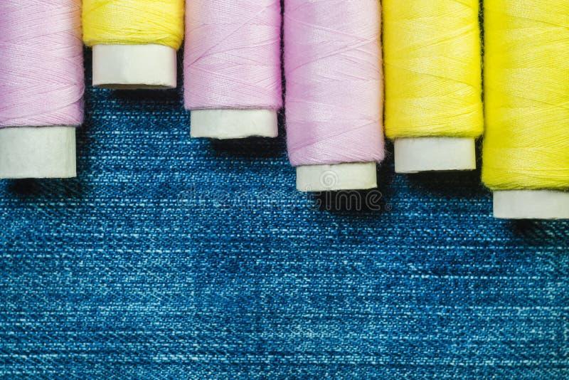 Rullar av den rosa och gula sy tråden på blå grov bomullstvill med kopieringsutrymme royaltyfri fotografi