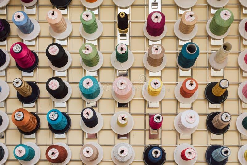 Rullar av tråden som hänger i en skräddare, shoppar Skeins för symaskinhängning i en sömnad shoppar arkivfoto