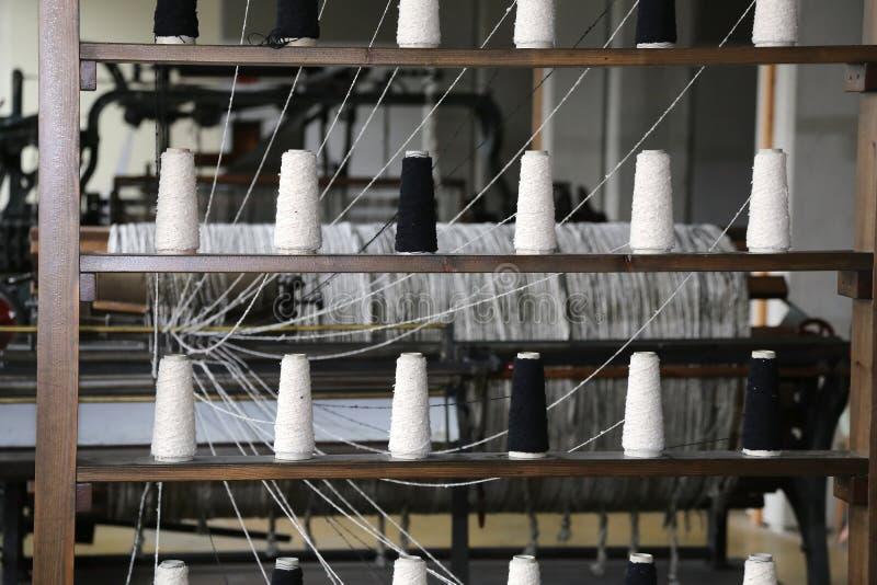 rullar av tråden som ska roteras i den gamla industriella väva vävstolfabren arkivbild