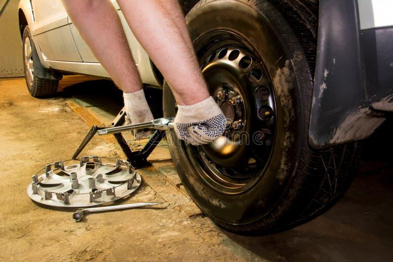 Rullar den ändrande bilen för mechanicianen i garage Man som utbyter gummihjulet Gummihjulservice arkivbilder