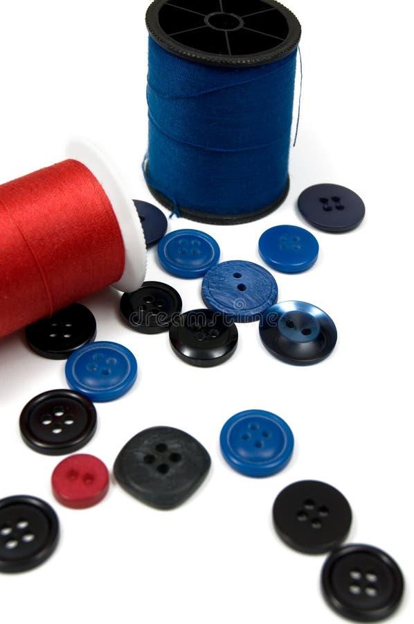 Rulle av den blåa och röda sy tråden med blåa och svarta knappar royaltyfri foto