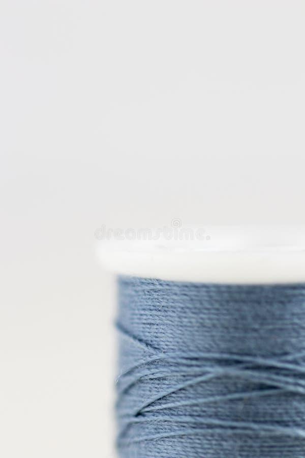 Rulle av den blåa tråden med den mycket inskränkta fokusen på vit bakgrund royaltyfria foton