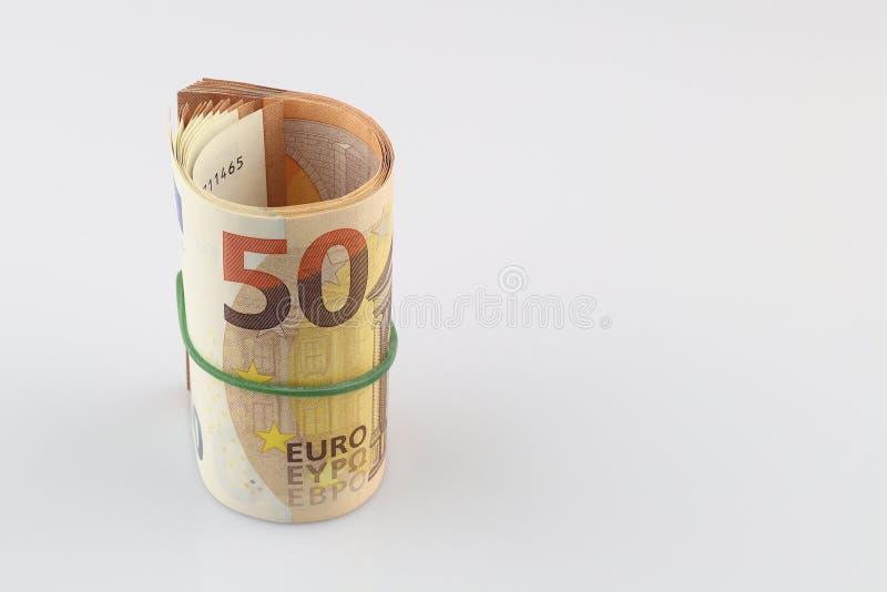 Rulle av femtio eurosedlar med en gummiband, isolerad bakgrund arkivfoton