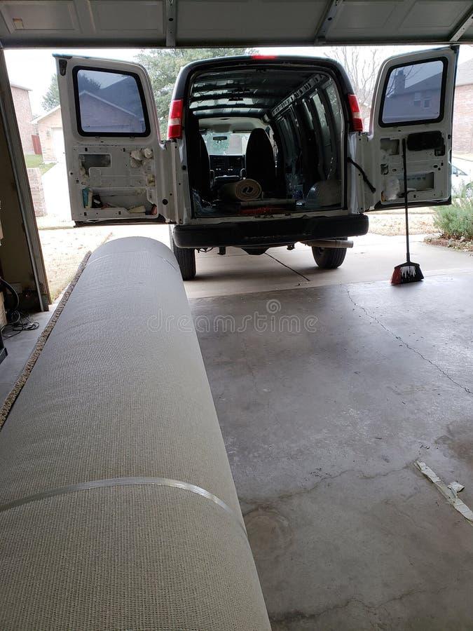 Rulle av ny matta i garaget av huset för att byta ut royaltyfri foto