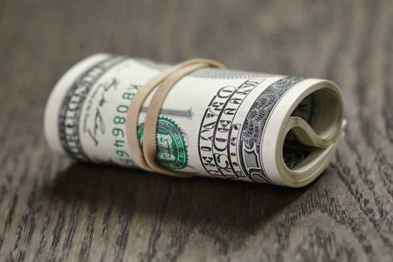 Rulle av ny stil hundra dollarräkningar på tabellen royaltyfri fotografi