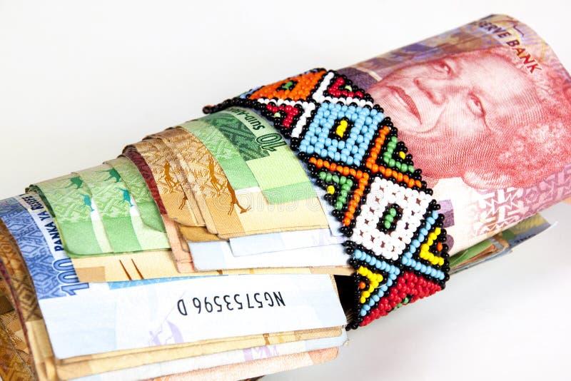 Rulle av söder - afrikanska sedlar som säkras med Zulu Beads arkivbilder