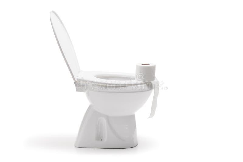 Rulle av toalettpapper på en keramisk toalettbunke arkivfoto