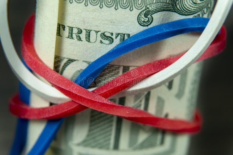 Rulle av USD räkningar med den röda, vita och blåa musikbandet royaltyfri bild