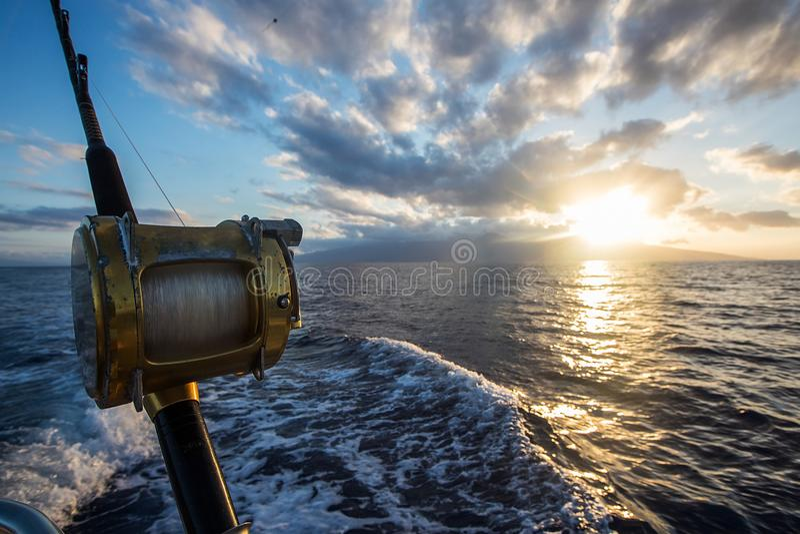 Rulle för fiske för djupt hav på ett fartyg under soluppgång royaltyfria bilder