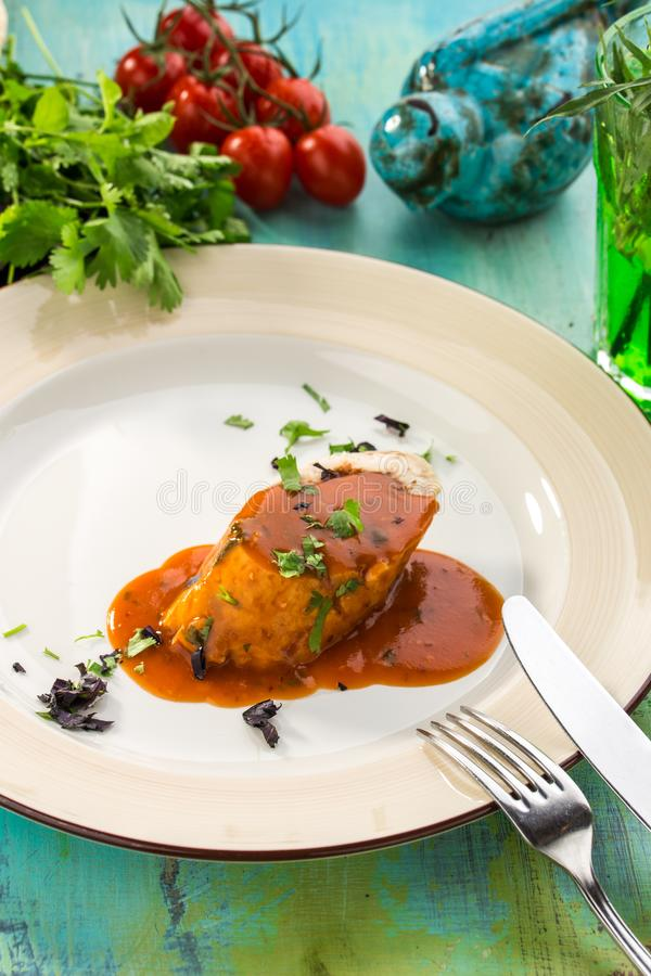 Rulle för grillat griskött som stoppas med andra kött och grönsaker på den blåa trätabellen royaltyfri fotografi