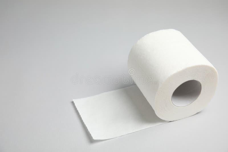 Rulle för toalettpapper på grå bakgrund royaltyfria foton