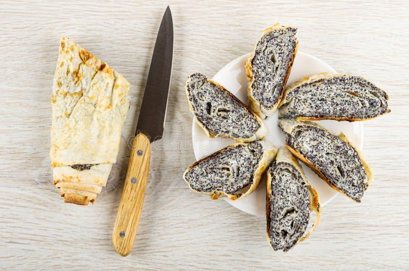 Rulle från pitabröd med påfyllning från keso, vallmo, kniv, skivor av rullar i platta på tabellen Top besk?dar royaltyfri fotografi