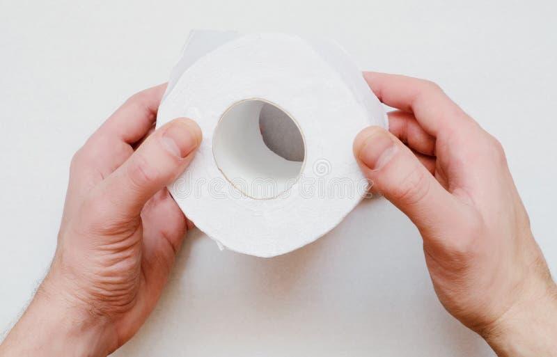 Rullen av toalettpapper i händerna fotografering för bildbyråer