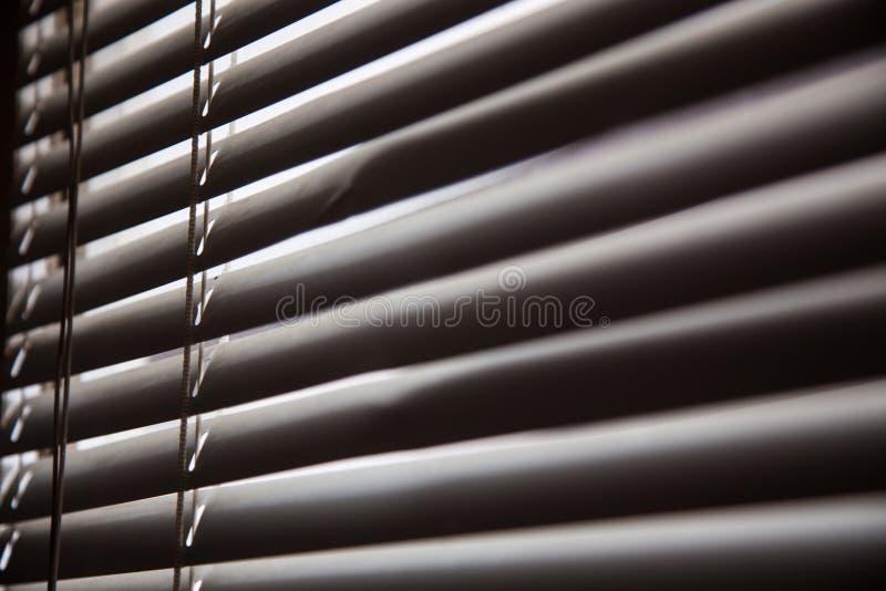 Rullgardiner i ett hem som fångar solljuset, baksida för metallslutarefönster royaltyfri bild