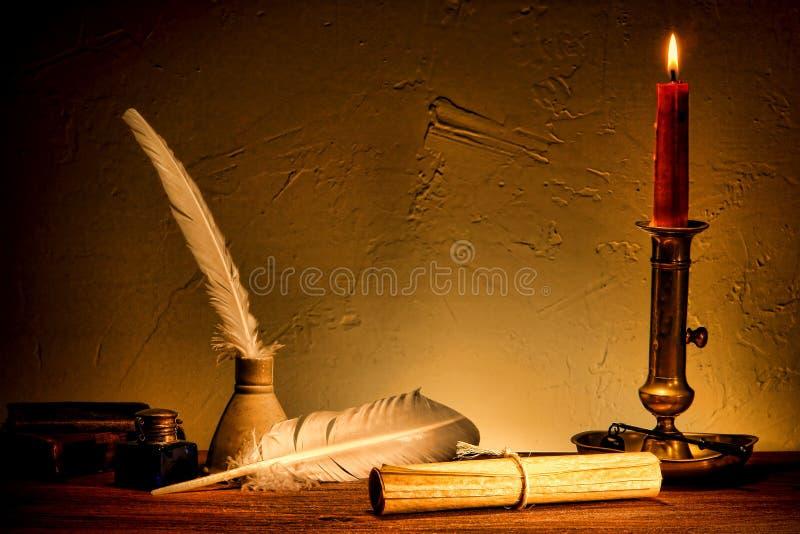 Rullo antico della carta pergamena dal vecchio indicatore luminoso della candela immagine stock