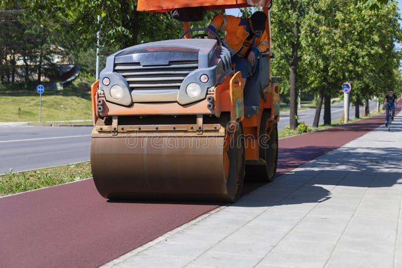 Rullo dell'asfalto che fa la nuova strada della bicicletta dall'asfalto rosso fotografia stock libera da diritti