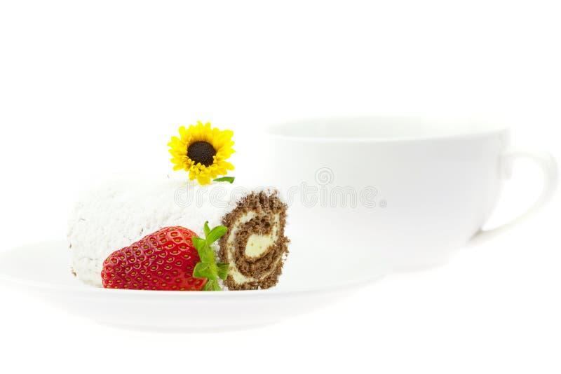 Rullo della torta, fragole e un fiore fotografia stock